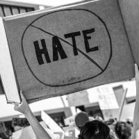 """Black and white photo of a person holding a cardboard sign that reads """"HATE"""" circled and crossed out. You can see the back of their head and back in a crowd of people."""