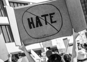 "Black and white photo of a person holding a cardboard sign that reads ""HATE"" circled and crossed out. You can see the back of their head and back in a crowd of people."