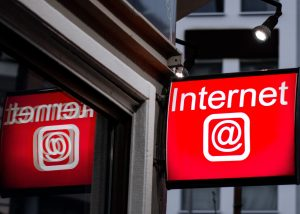 "Photo of a red sign on a building that reads ""Internet @."" The sign reflects on the window."