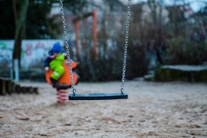 Photo of a playground swing empty. In the background is a child in bright clothing but they are blurry and you can not see their face