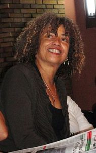 Photo of Angela Davis smiling. they are wearing a black coat and shirt.