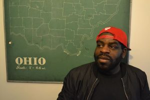 Photo of Hanif Abdurraqib. They are wearing a red baseball hat backwards. behind them is a green poster.