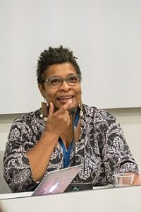 Photo of Nalo Hopkinson. They are smiling and have their hand on their chin. They are wearing glasses and a patterend shirt. behind them is a blank whiteboard.