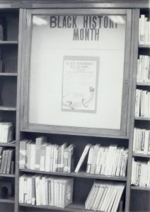 "Black and white photo of a library shelf and display that reads ""BLACK HISTORY MONTH"" You can see a poster that reads ""black experience"" but you can not make out the other words on the poster.t"