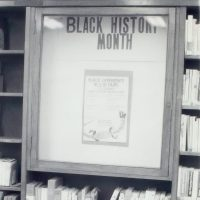 """Black and white photo of a library shelf and display that reads """"BLACK HISTORY MONTH"""" You can see a poster that reads """"black experience"""" but you can not make out the other words on the poster.t"""