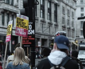 "Photo of a group of people standing in a street with signs that read ""stop racist attacks! Unite and Fight"" You can only see the backs of people."