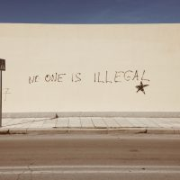 """Photo of a white wall that is spray painted to read, """"No one is illegal."""" There is a blue sky above the wall and white sidewalk."""