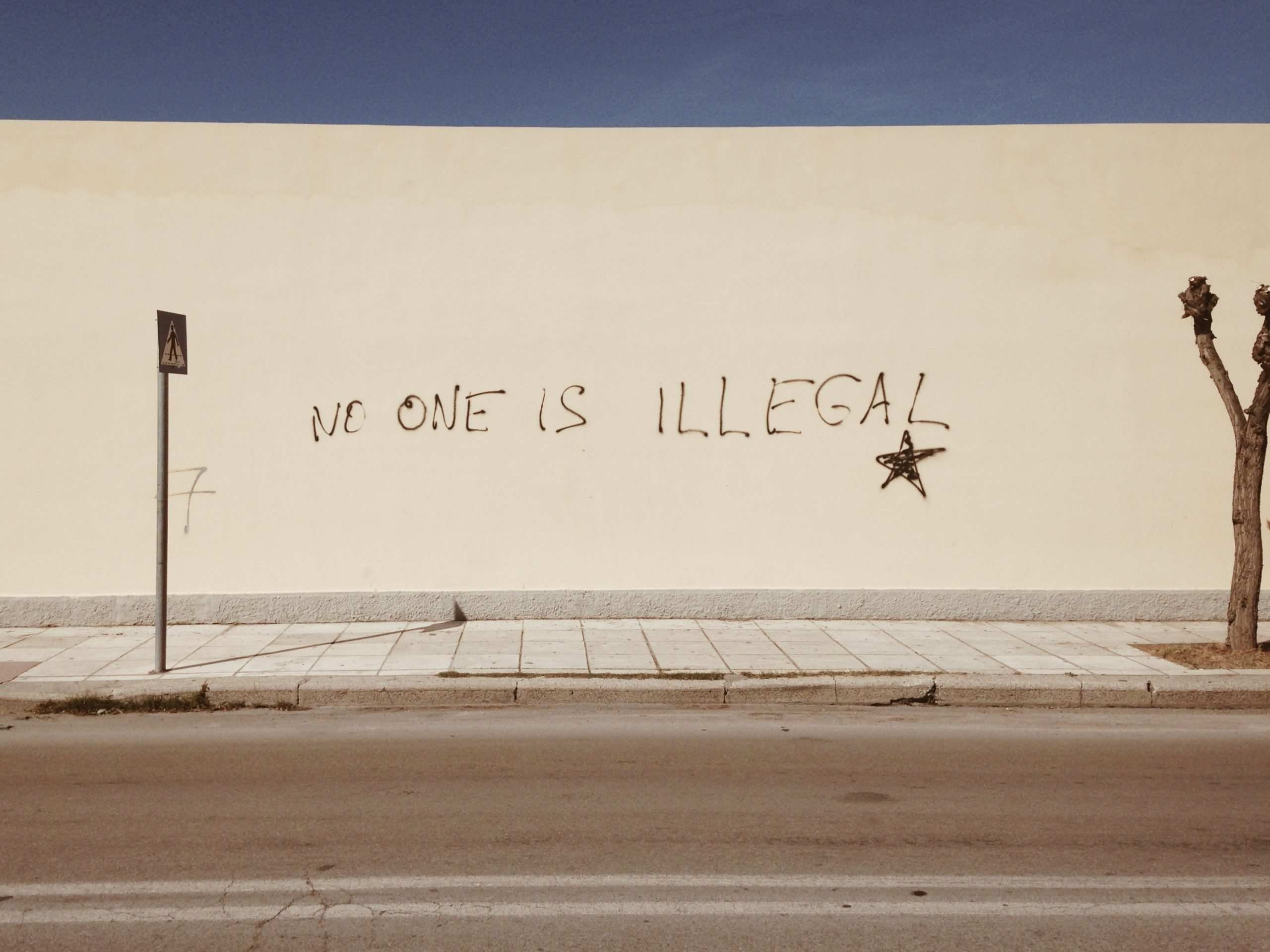 "Photo of a white wall that is spray painted to read, ""No one is illegal."" There is a blue sky above the wall and white sidewalk."