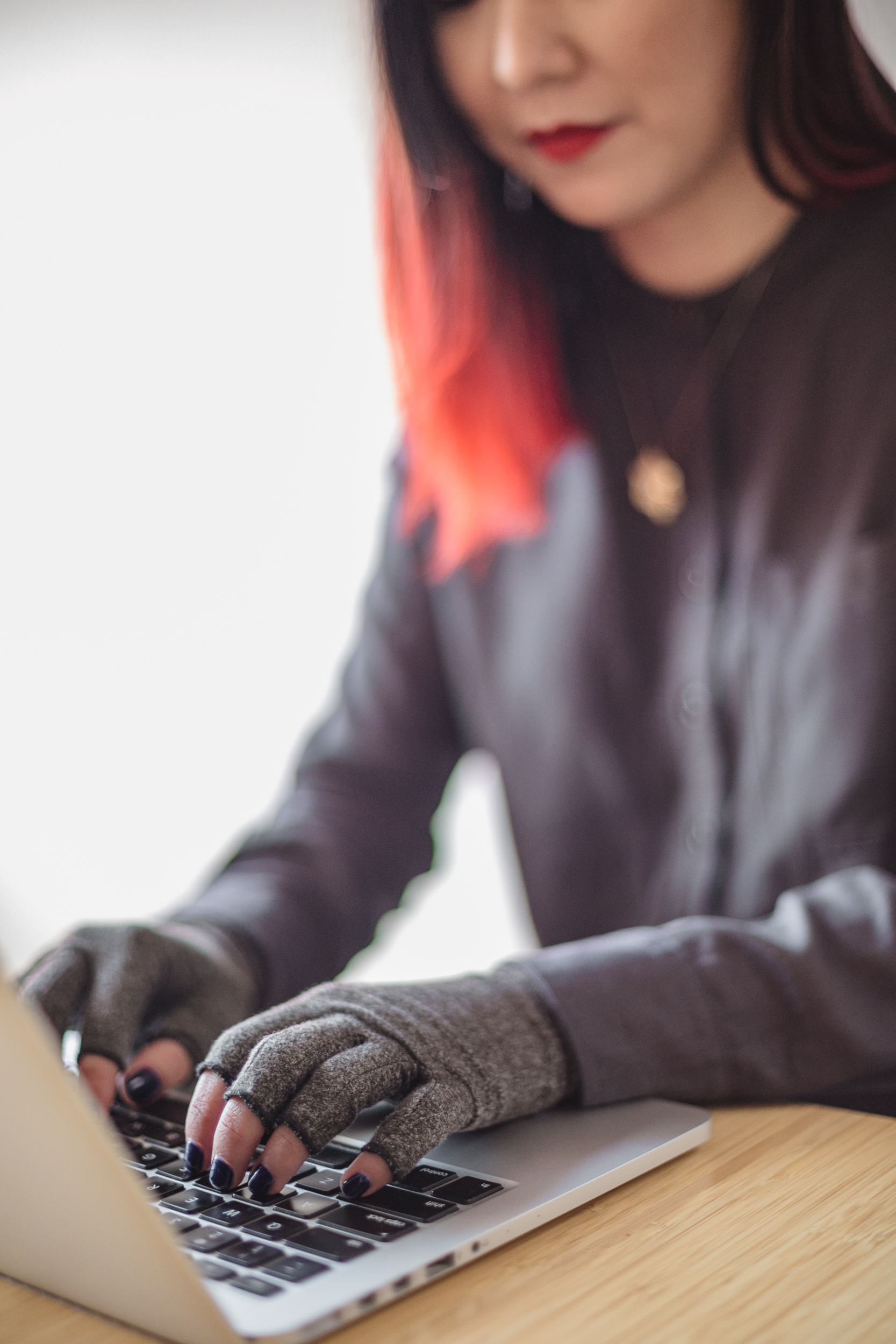 An Asian disabled woman types on a laptop while wearing compression gloves. The hands and keyboard are the focal point.