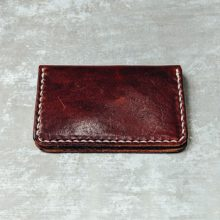 Small burgundy wallet on gray background
