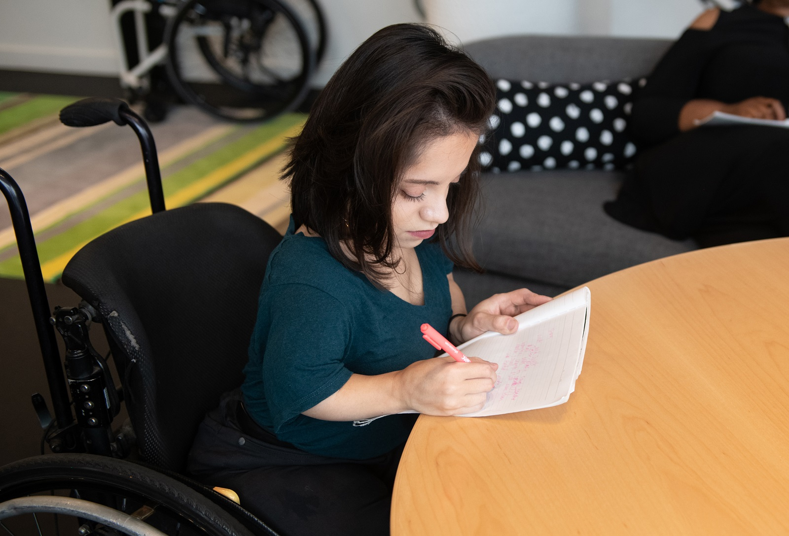 A South Asian person in her wheelchair takes notes by hand during a meeting.