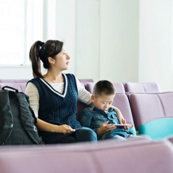 Adult with ponytail and dress sitting with young child in a waiting area