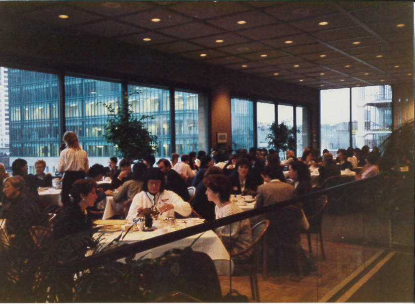 A room with big open windows. There are numerous small tables filled with people eating breakfast together.