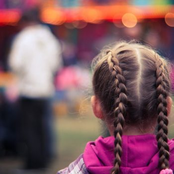 rear view of a young girl wearing a pink sweater with two braids, colourful background and out of focus individual in the background