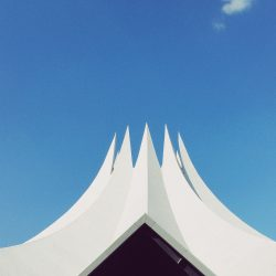 Image of a white tent with multiple points at the top with a bright blue sky and one cloud in the background Photo Credit: Pavel Nekoranec on Unsplash Blog