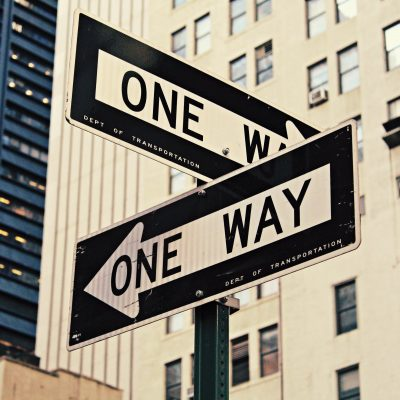 "Street Signs that both read ""One Way"" pointing in different directions"