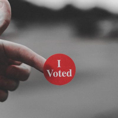 """Image of a sticker saying """"I Voted,"""" on the tip of an unseen person's finger"""