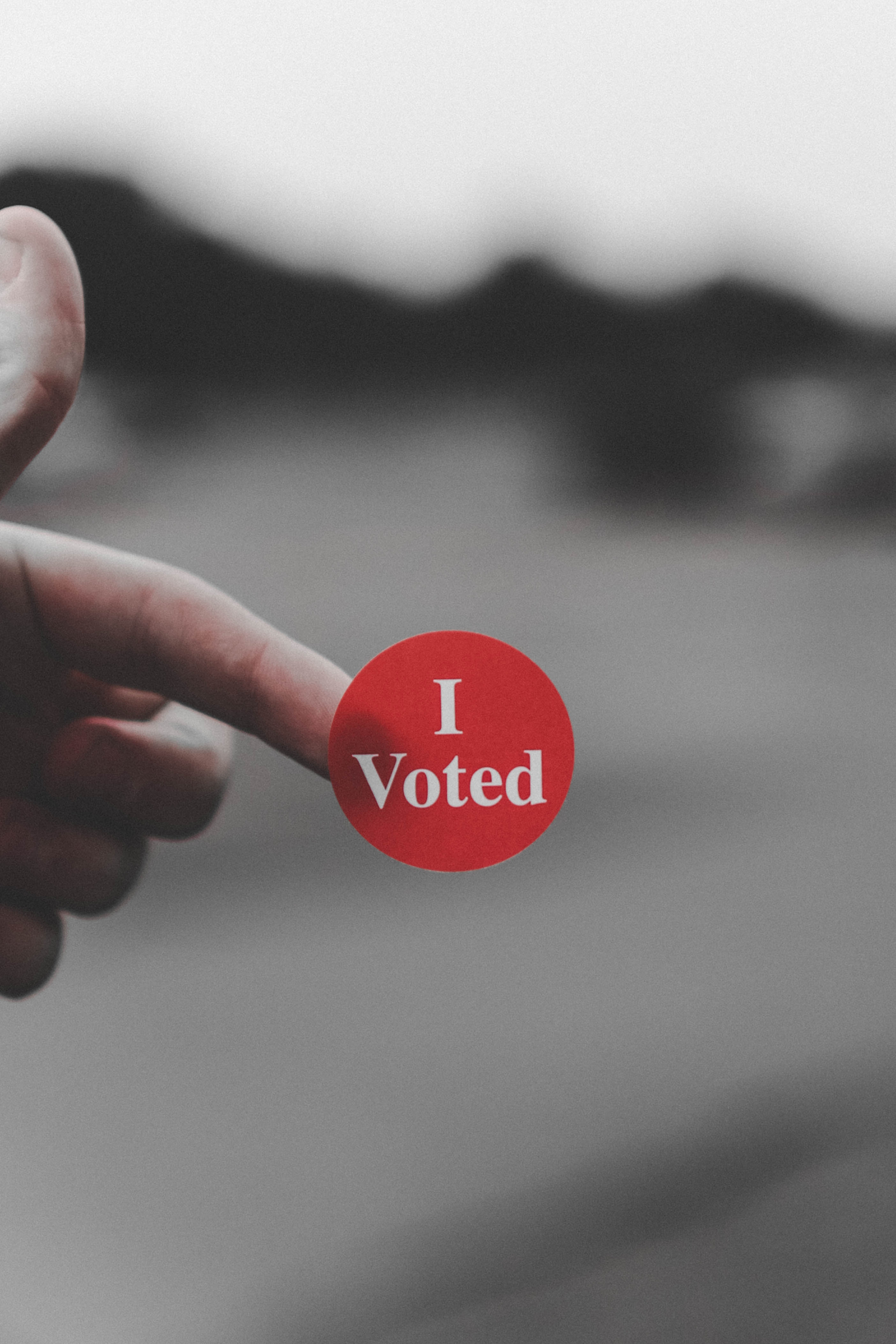 "Image of a sticker saying ""I Voted,"" on the tip of an unseen person's finger"