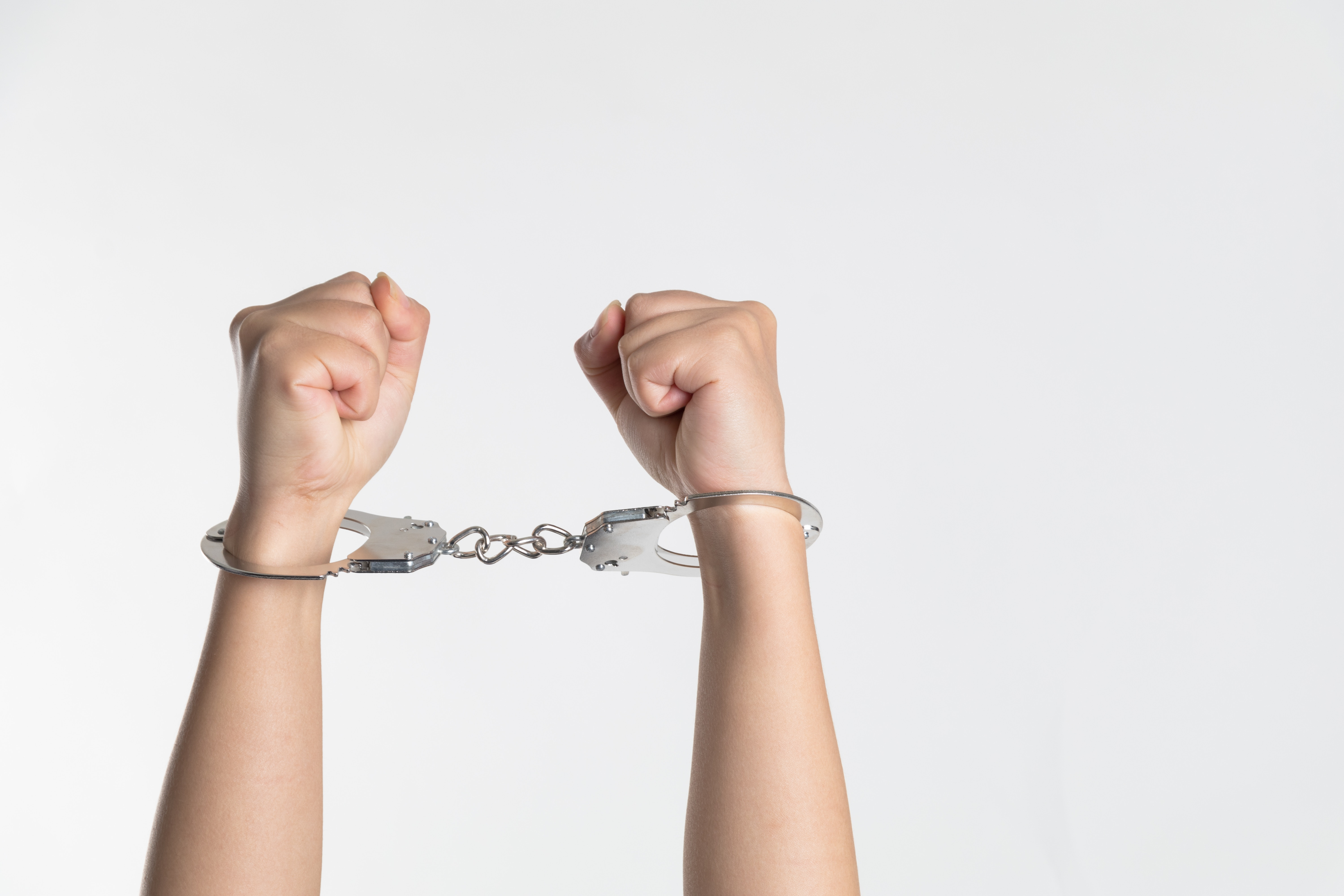 Photo of arms raised as fists in the air with handcuffs on each arm