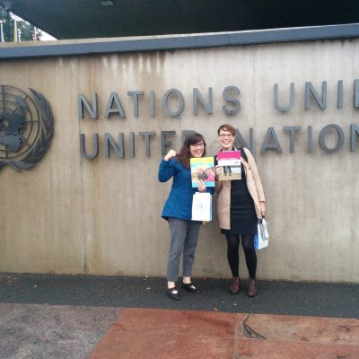 """Two people are standing in front of a large sign that says """"Nations Unies United Nations."""" One is holding the High Stakes report by West Coast LEAF about child care and the human rights of women and children. The other is holding the 10aDay Child Care plan and has her fist raised."""