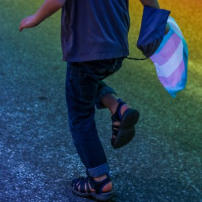 The lower part of a child (viewed from the back) running on a road carrying a trans flag with pink, blue and white stripes. There is a projection of rainbow-coloured light on the road.