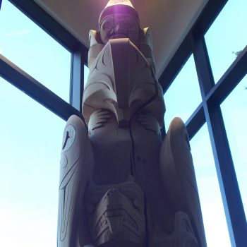 The upper part of a totem pole, viewed from below. It appears to be in the corner of a room with windows behind it and the blue sky visible through the windows.