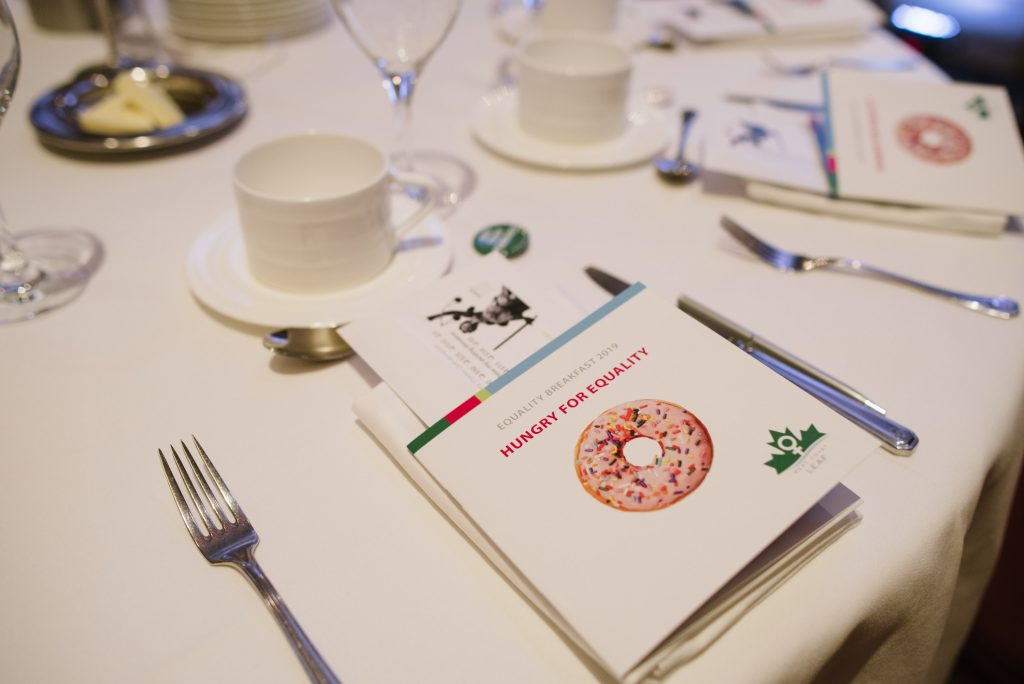 """a place setting is featured in this photo. at it are flatware, coffee cup, and a pamphlet that reads """"equality breakfast 2019: hungry for equality"""" from west coast leaf"""