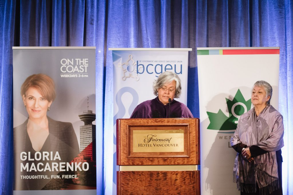 an individual stands at a podium speaking into a microphone. on the right an individual stands. the background shows banners for cbc, the bcgeu and west coast leaf