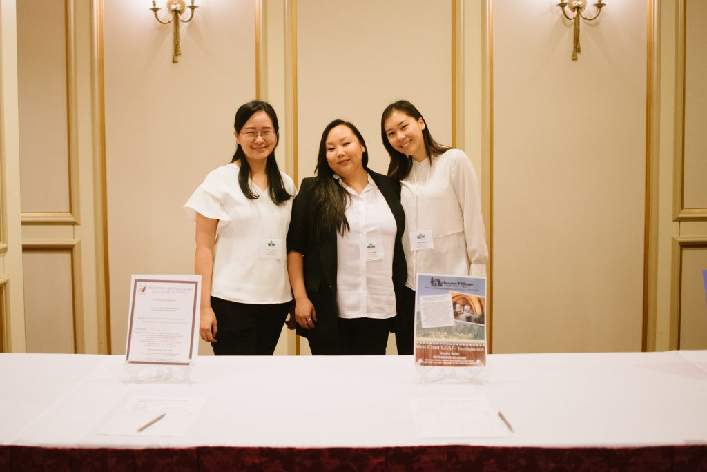 three individuals stand together in front of a table with information on it.