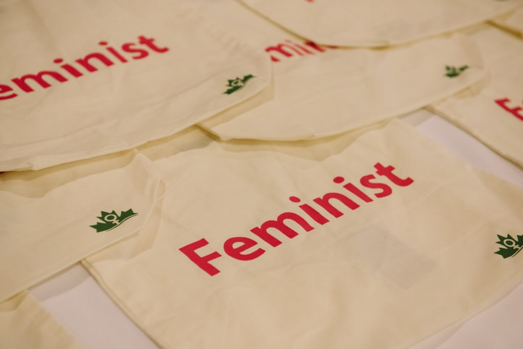 """cream-coloured tote bags bearing the word """"feminist"""" and the west coast leaf logo"""