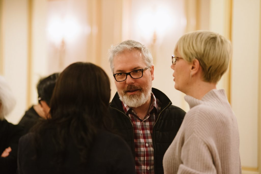 two individuals stand talking to another event attendee who is facing away from the camera