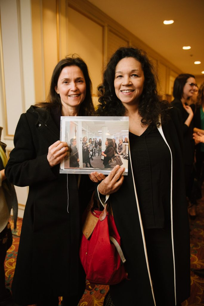 two individuals stand together, smiling. they are holding up a photo of what may be a similar event or gathering where attendees are talking together.