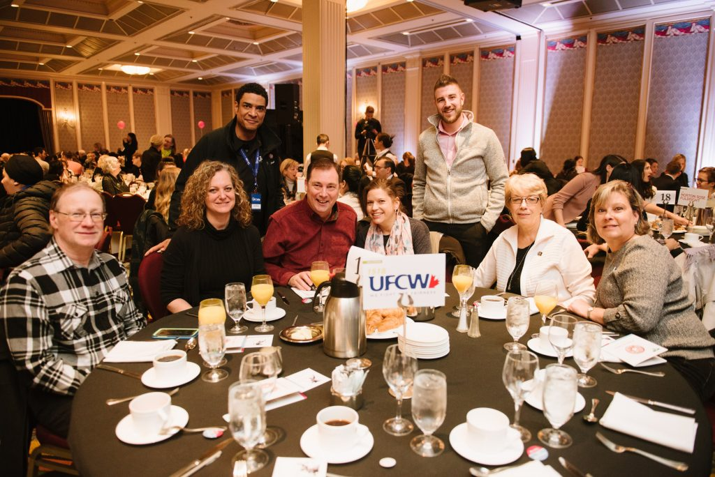 six individuals are seated together at a circular table during an event. two individuals stand behind them. the sign on their table is for the ufcw in the background are fellow attendees within a banquet hall