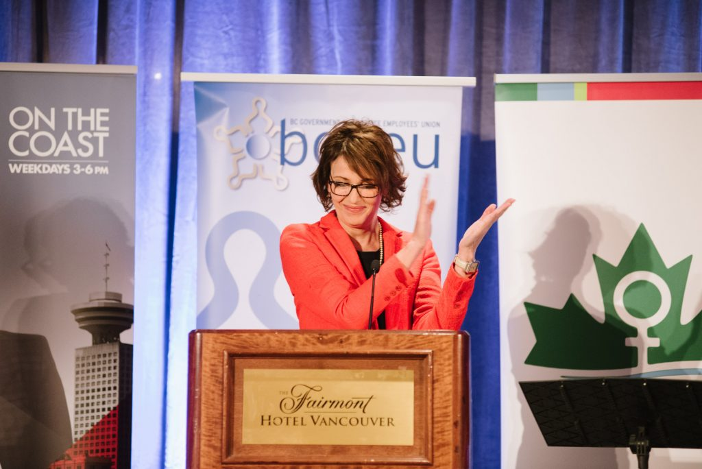 a smiling individual stands at a podium behind the microphone. they are applauding. in the background are banners for cbc, the bcgeu, and west coast leaf