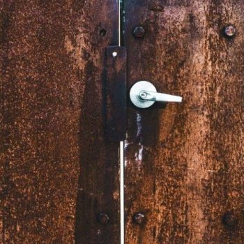 A rust-looking brown metal door with a silver-coloured metal door handle. Photo by Ava Neue, Division 7 Studios.