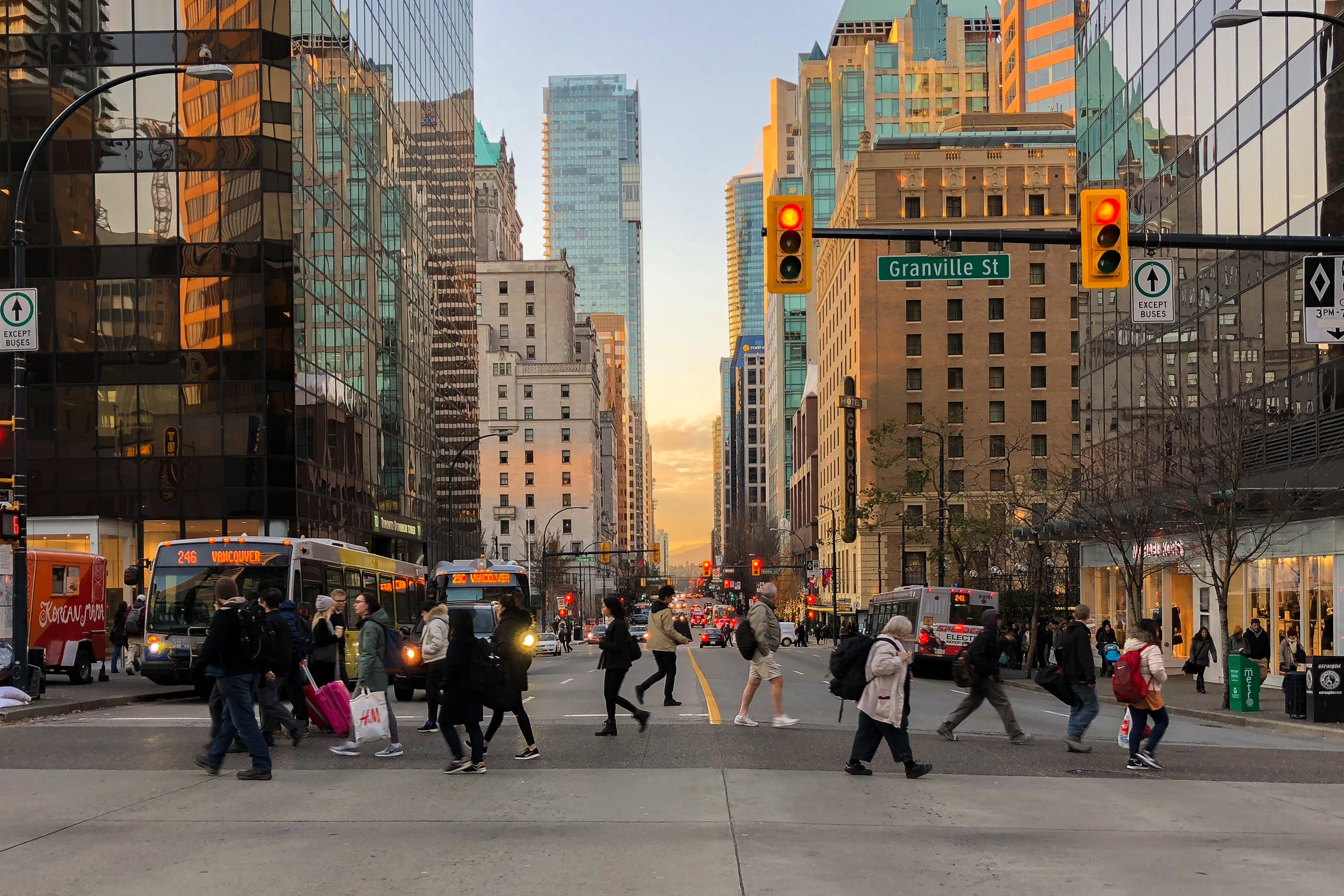 Photo of people crossing a busy intersection surrounded by tall towers