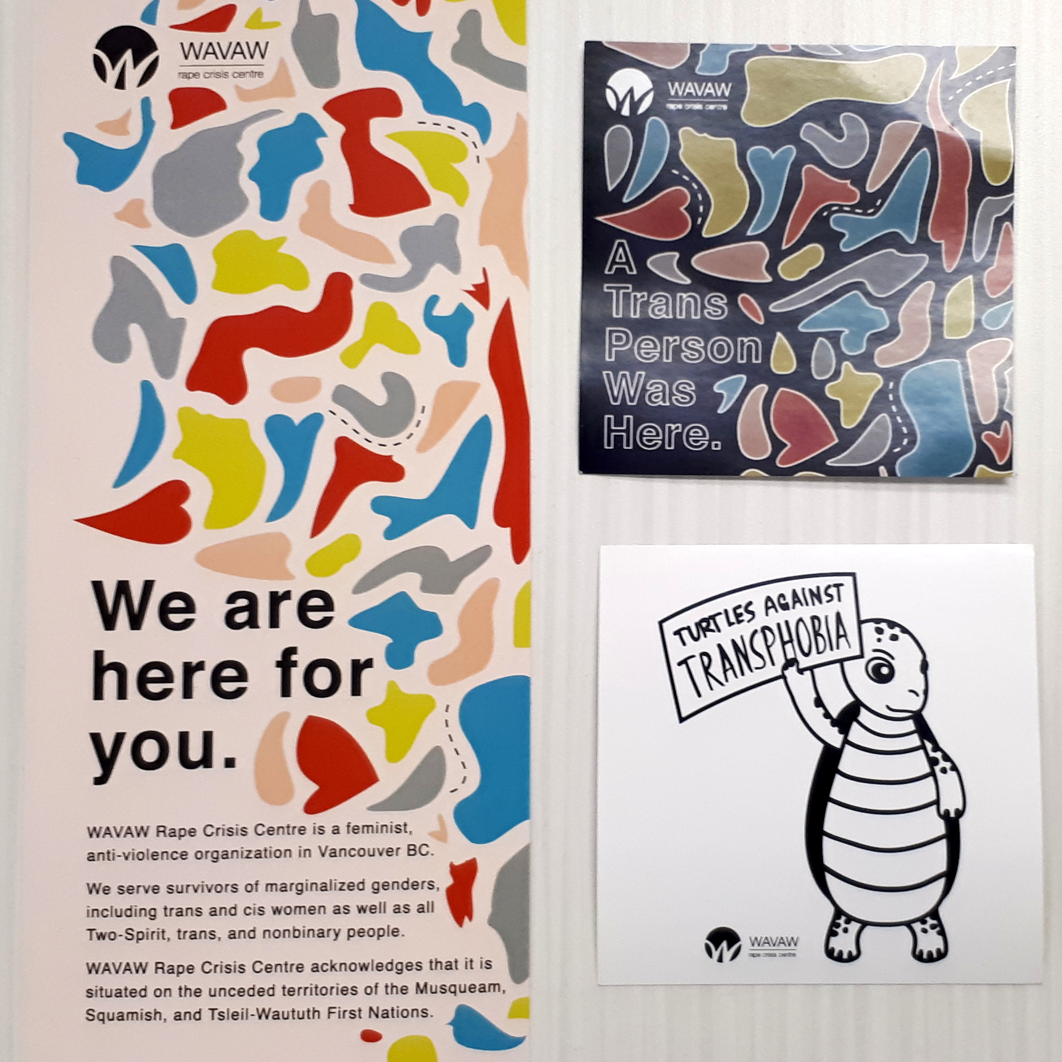 """Photo of three posters on a wall. One says """"We are here for you,"""" one is a drawing of turtle that reads """"turtles against transphobia,"""" and the last one reads """"a Trans person was here."""""""