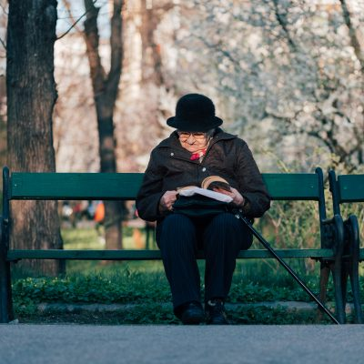 Photo of an older adult reading in a park on a park bench wearing a black hat and coat