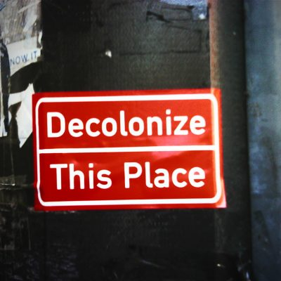 "Photo of a red sticker on a black wall. In white writing the sticker reads "" Decolonize This Place"" With Decolonize on the line above this place."