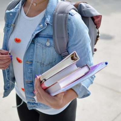 Photo of a person's torso wearing a jean jacket and backpack and carrying a book and binder