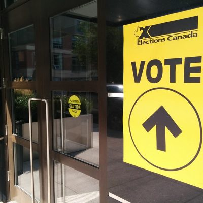 """Photo of a clear glass door with a yellow Elections Canada sign that reads, """"VOTE,"""" with an arrow pointing straight"""