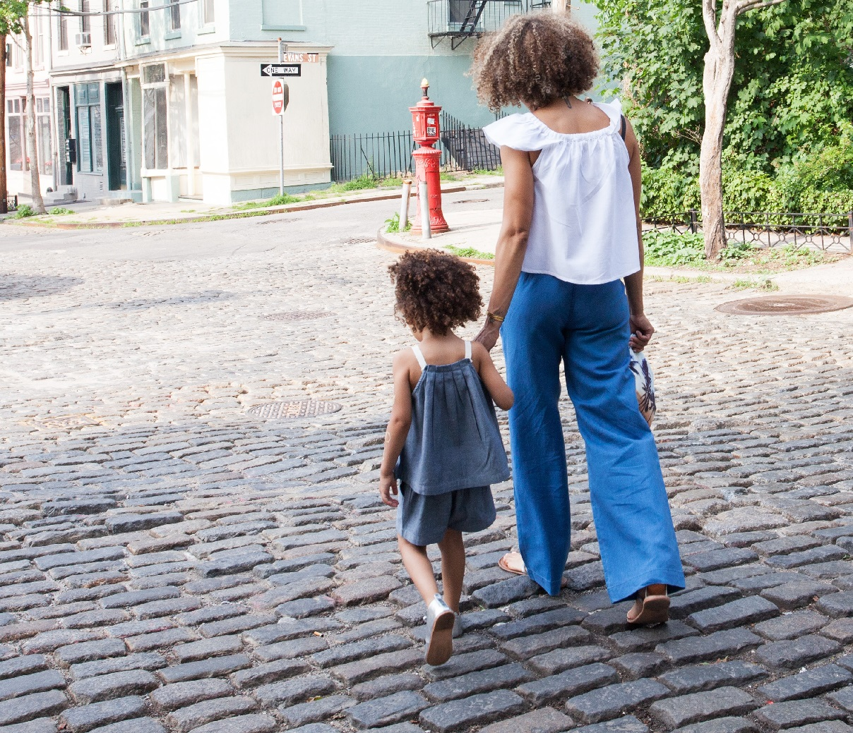 Photo of a person holding a child's hand. They are walking on a cobble stone street.