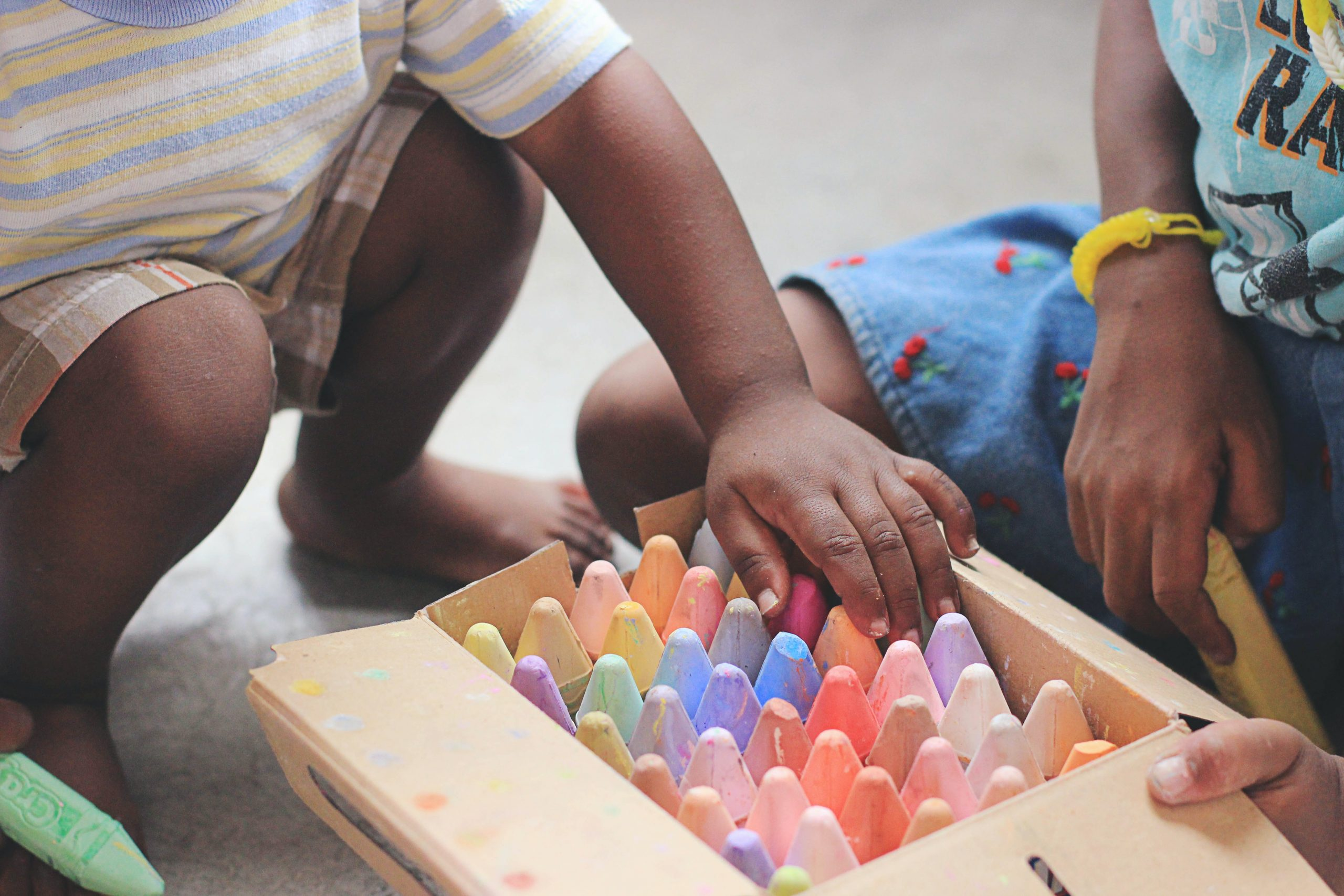 A child is reaching into a box of chalk with another child beside them.