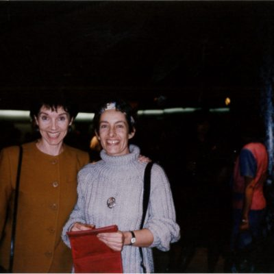 Two women standing together and smiling.