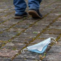 Blue surgical mask dropped on a brick road. Person's feet appear to be walking away from it.