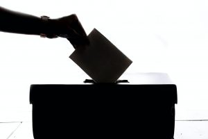 A person's hand dropping their voting card into a box