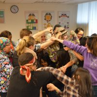 Youth facilitator volunteer trainees forming a human knot and trying to get untangled. The photo has a playful and collaborative vibe.